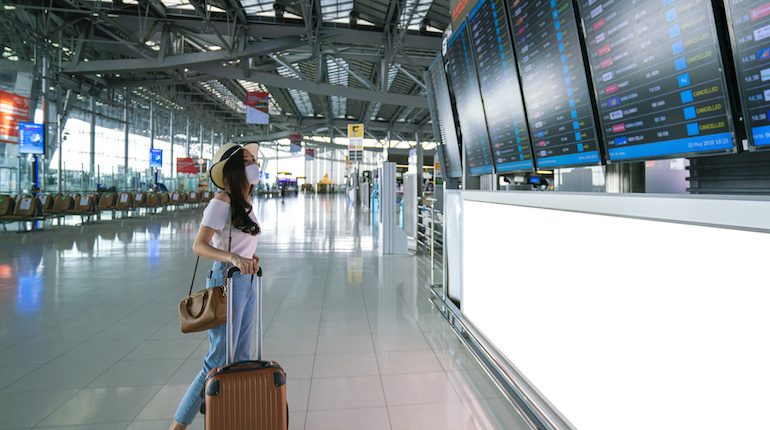 Asian female wearing face mask with suitcase checking flight cancellation status on airport information board in empty airport. airline bankrupt, airline crisis, coronavirus or new normal concept