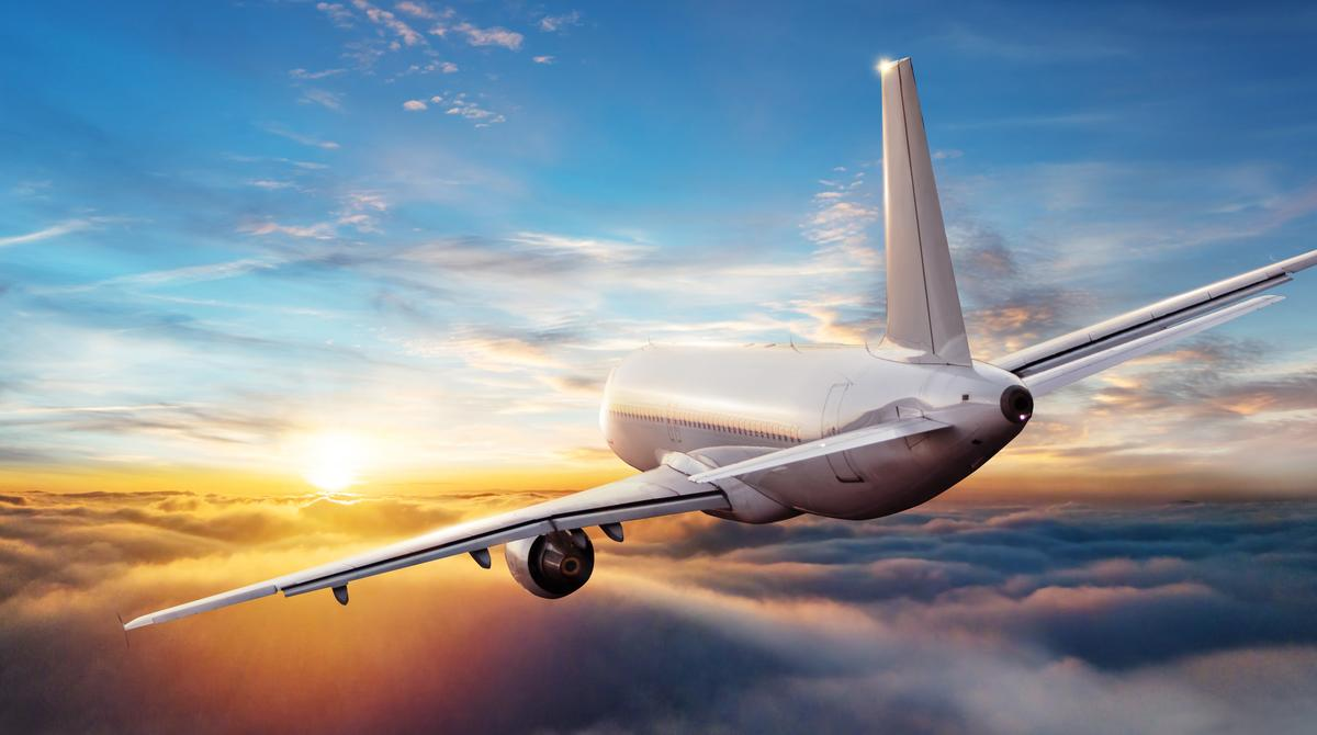 Commercial airplane jetliner flying above clouds in beautiful sunset light. Travel and business concept. Backside view