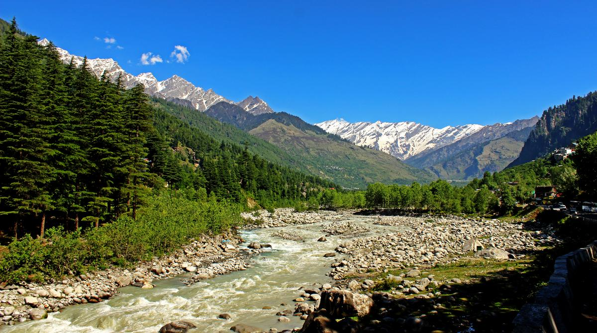 Snow clad himalayas viewed from The Beas River in Manali from Leh - manali highway in summer morning of May, India.Himachal Pradesh