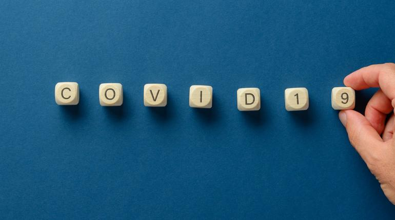 Wide view image of male hand making a Covid 19 sign spelled on wooden dices. Over blue background.
