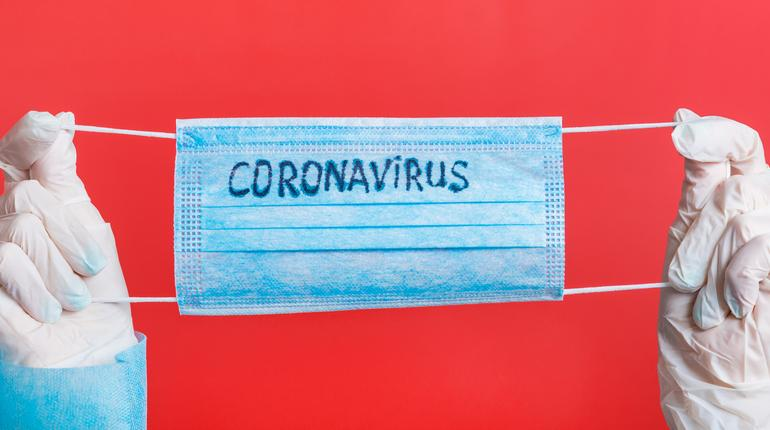 Female hands in medical gloves holding protective mask with coronavirus text on it at red background. Health care concept. Coronavirus concept.