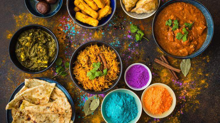 Traditional Indian food, Holi colours powder, rustic background. Indian Holi holiday. Indian dishes and snacks set. Holi celebration. Top view. Festive Indian table setting. Party food selection