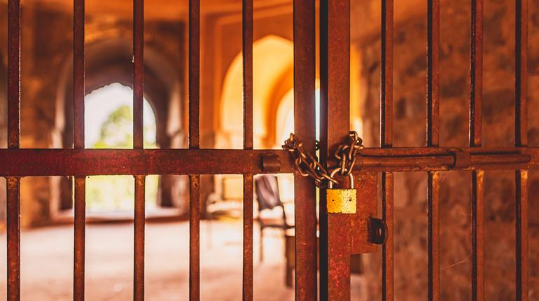 A locked metal door with bars at an ancient monument in Delhi, India. A famous old fort known as Purana Qila or Quila. Vintage concept.