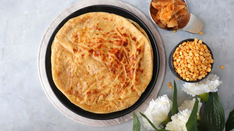 Holi Festival Food - Puran Poli is an Indian sweet flatbread stuffed with mixture of chana dal, jaggery, ghee & cardamom. Usually eaten on Holi or Gudi Padva festival. Recipe ingredients. copy space.