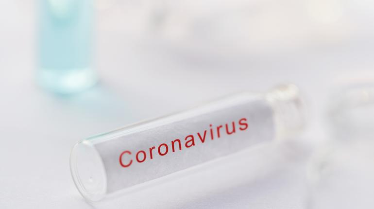 Coronavirus testing kit background. Blank test tube or glass vile over white laboratory desk for collecting blood sample of chinese virus covid-19 infected persons with copy space.
