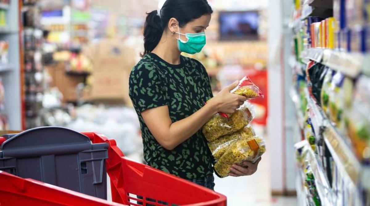 Alarmed female wears medical mask against coronavirus while grocery shopping in supermarket or store- health, safety and pandemic concept - young woman wearing protective medical mask for protection from virus covid-19 and stockpiling food