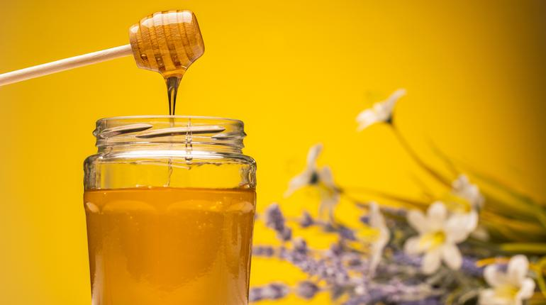 glass jar full of honey and dipper on wooden table with flowers on background