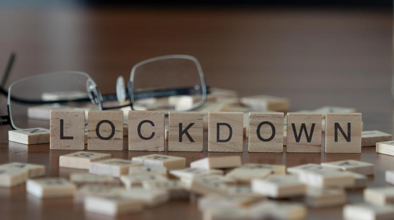 lockdown concept represented by wooden letter tiles on a wooden table with glasses and a book