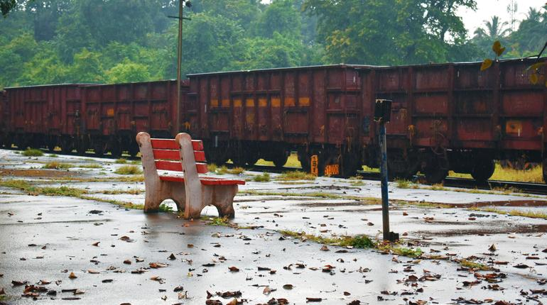 empty bench with leaves around in a railway station in goa India