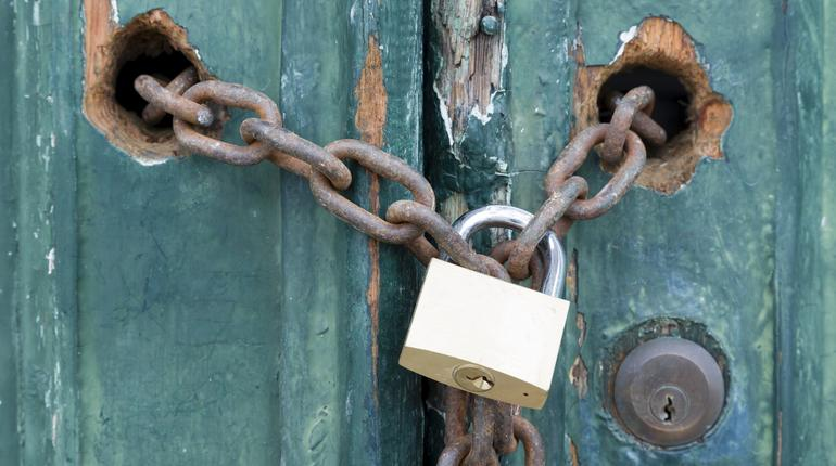 Padlock and chain on an old door, illustrating concepts of security and encryption