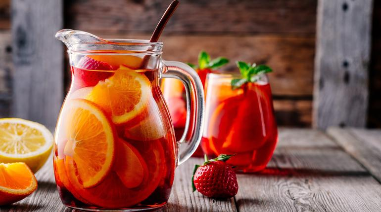 Homemade red wine sangria with orange, apple, strawberry and ice in pitcher and glass on rustic wooden background
