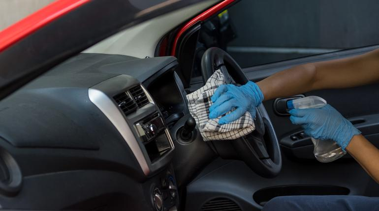 Cleansing car interior and spraying with disinfection liquid. Hands in rubber protective glove disinfecting vihicle inside for protection from virus disease