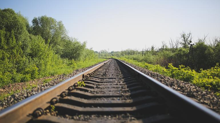 Rail tracks in the green field. Railway transport industry. Empty road on summer day. Travel lifestyle motivation photo.