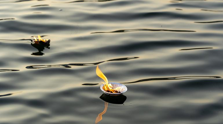 Hinduism religious ceremony puja flowers and candle on the sacred river Ganges water in Rishikesh, India, close up