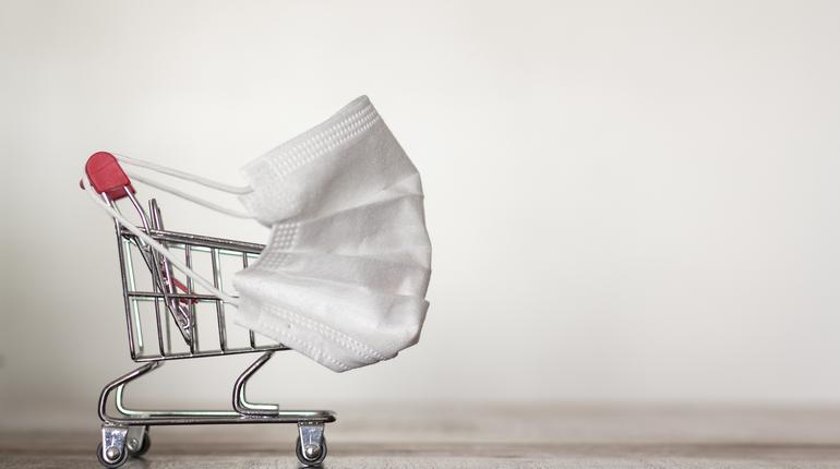 Shopping trolley with medical mask. Coronavirus pandemic, COVID-19 shopping concept. With copy space
