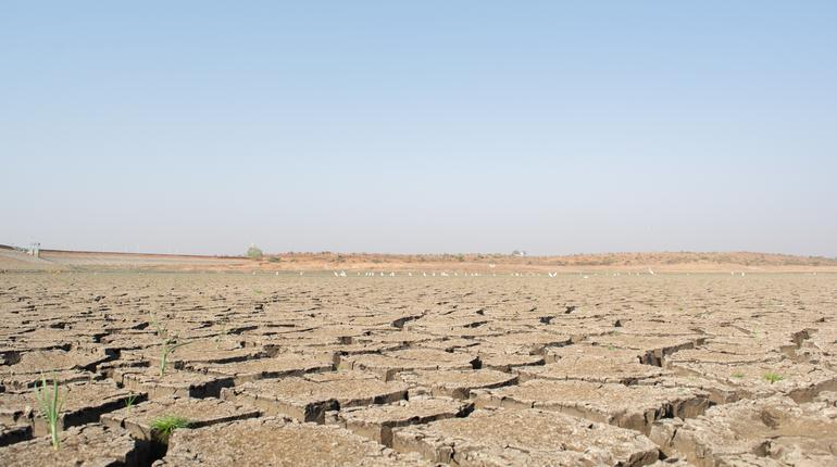 A dried up empty reservoir or dam during a summer heatwave, low rainfall and drought in north karnataka,India.