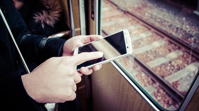 電車の車内でスマートフォンを使う女性