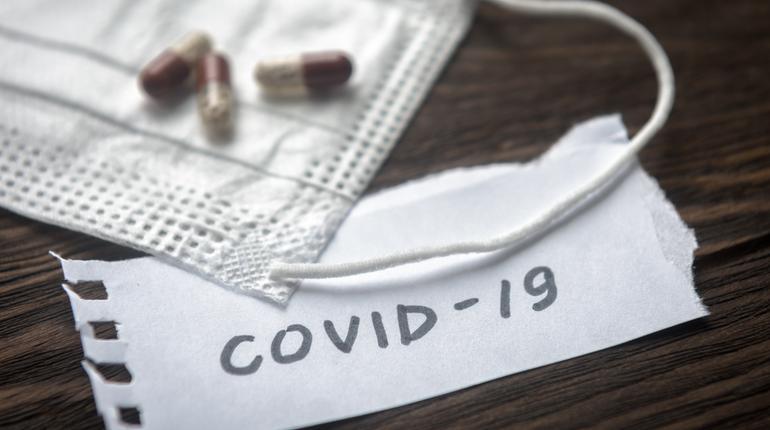 Coronavirus concept. Note COVID-19, Protective medical mask and pill capsules for treatment coronavirus. Novel corona virus outbreak. Epidemic from Wuhan, China. Coronavirus drugs on wooden table.