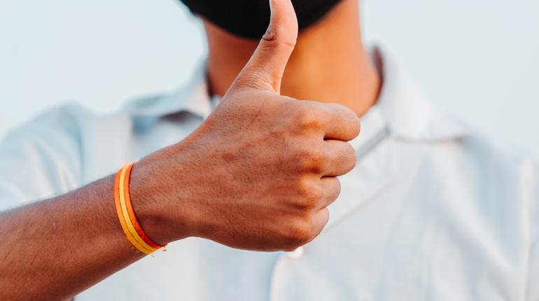 Closeup of hand of an Indian doctor showing thumbs up during the corona virus pandemic