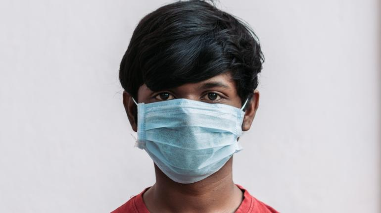 Closeup shot of an Indian kid wearing surgical mask to protect himself from infection of Corona Virus