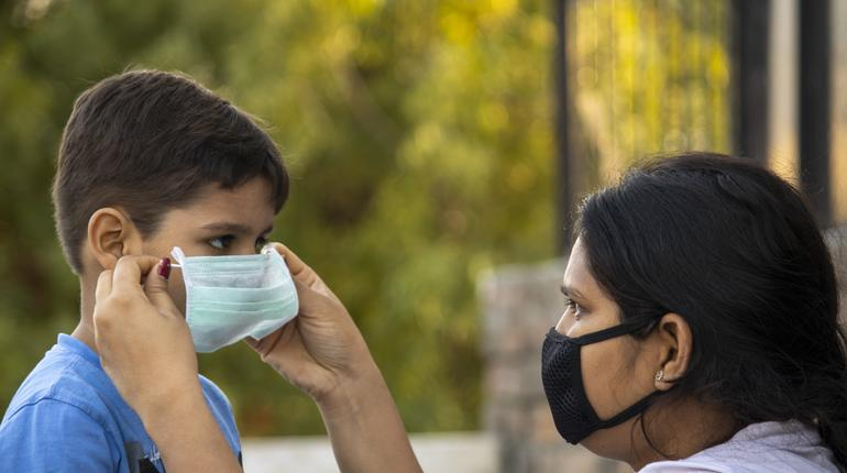 Mother help child to wear mask in india to protect him against flu and virus