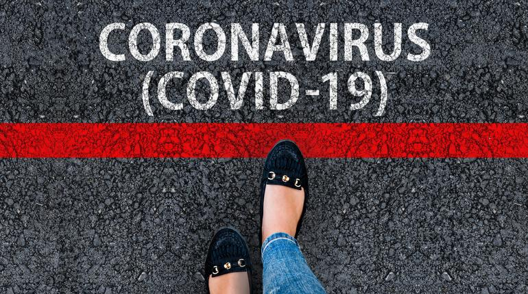 A woman steps to red line and words Coronavirus COVID-19 on asphalt road