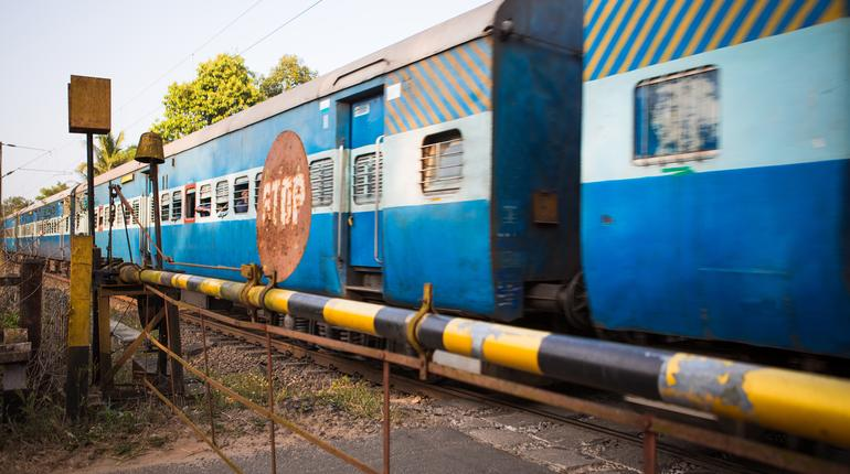 Old railway in India, Kerala. Rusty Stop sign, long train with cars, railway crossing barrier