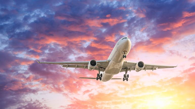 Commercial airplane flying in beautiful sky at sunset,travel concept.