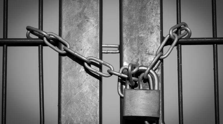 Padlock with steel chain closed iron fence symbolizing lockdown