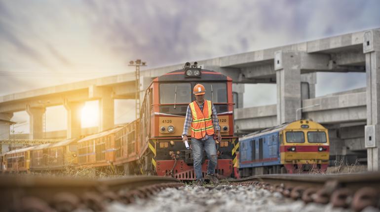 worker on railways with  locomotive  on background.