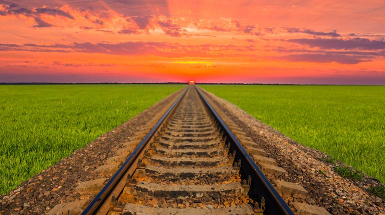 railway among green fileds leaving far to a dramatic sunset
