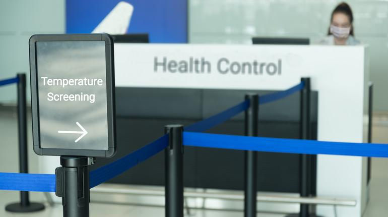 temperature screening sign at airport with woman wearing mask sitting at health control counter