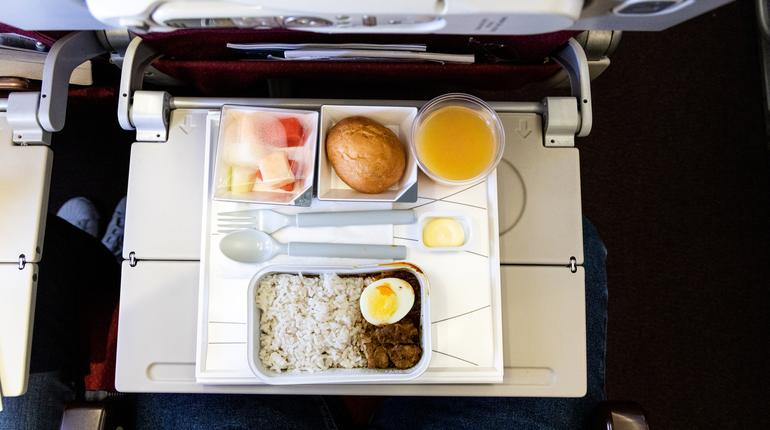 Overhead view of basic inflight meal of economy class consisting rice, egg, beef curry, bread, fruits, and juice.