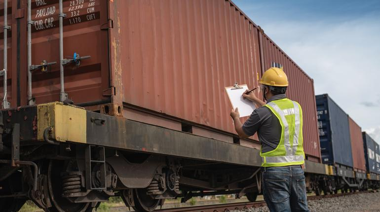 Male engineer, worker inspection checking on container on the train.