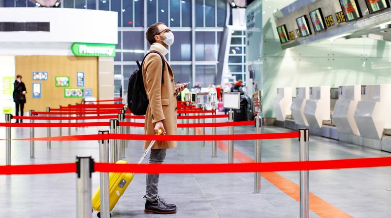 Man in mask at empty airport with luggage in coronavirus quarantine isolation, waiting for departure, flight cancellation, pandemic infection worldwide spread, travel restrictions and border shutdown