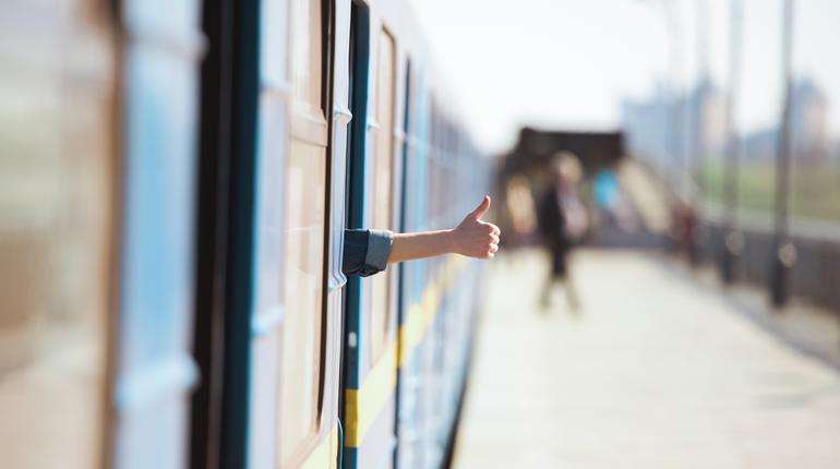 cropped image of female hand looking out from train and doing thumb up gesture at outdoor subway station