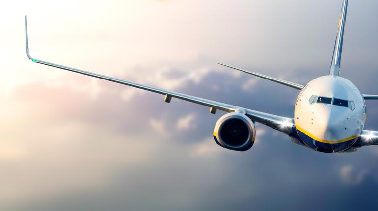 Close up of commercial passenger airplane flying above the clouds at sunset