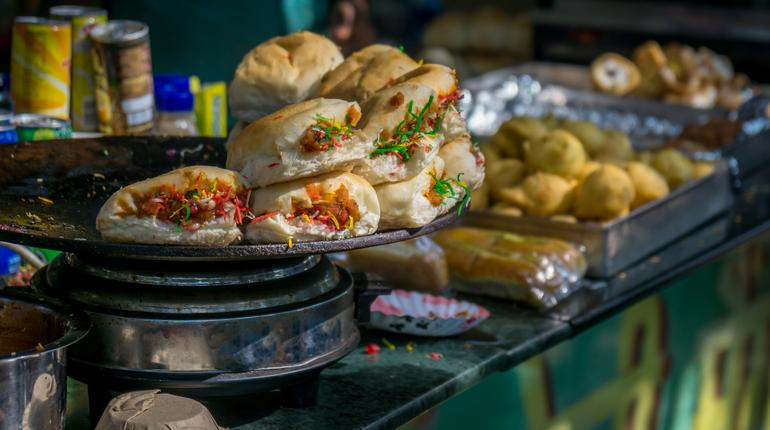 "The snack in focus is called ""Dabeli"" and the snack in the background is called ""Vada Pav"""