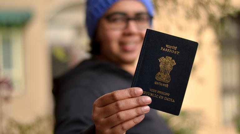 Portrait shot of a young beautiful Indian woman wearing blue cap holding her passport with her face blurred. Concept shot depicting happy traveler ready to go for an international vacation in winters