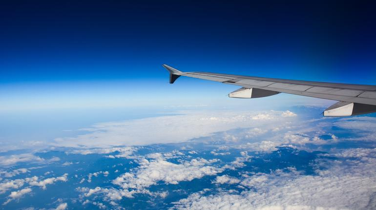 Wing of airplane over white clouds in sunny day.