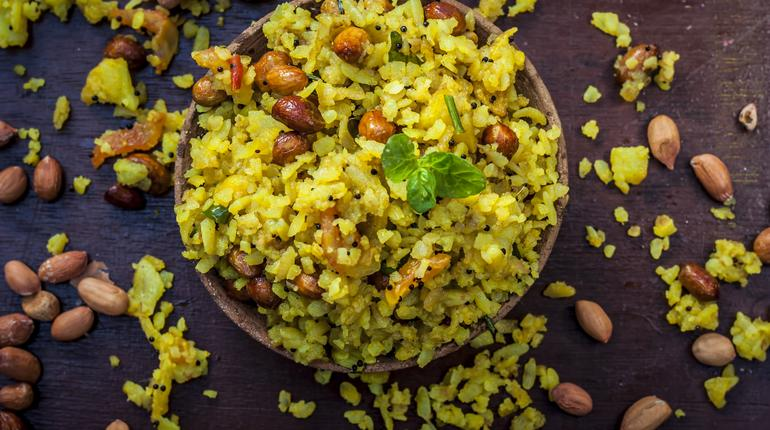 Close up of Indian popular brunch dish in a clay bowl with dried fried groundnut on it is Poha batata or Pava batata on a wooden surface in dark Gothic colors.