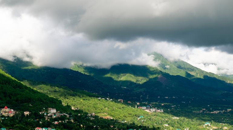 Hill station in india with buildings and grass covered hills with shadows of clouds falling on them. Shot at famous hill stations like shimla, jammu kashmir, himachal and more it shows a perfect vacation spot