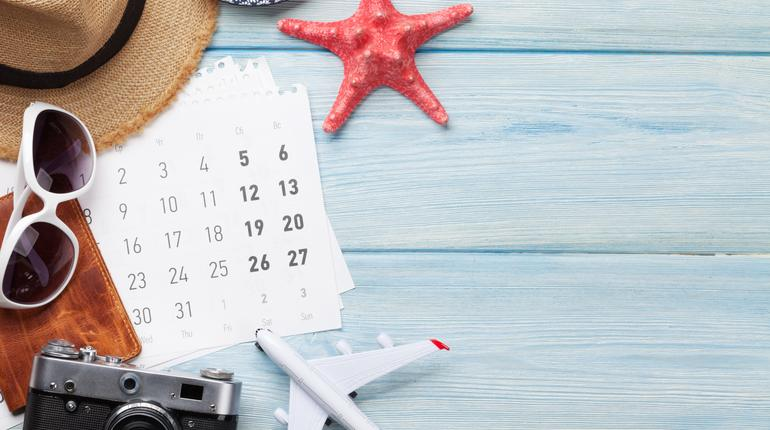 Travel vacation background concept with sunglasses, hat, camera, passport, airplane toy and calendar on wooden backdrop. Top view with copy space. Flat lay