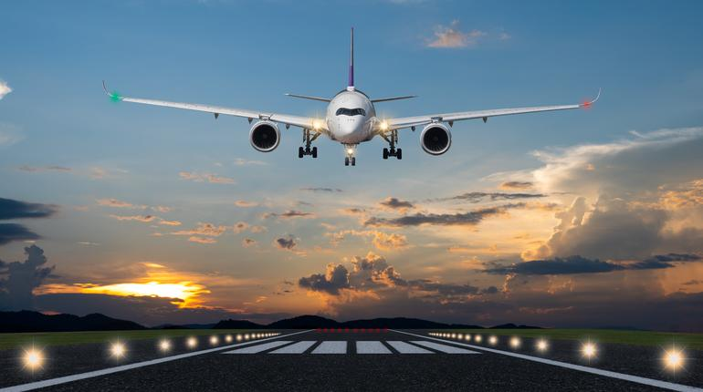 Airplane landing in the evening with beautiful sunset background
