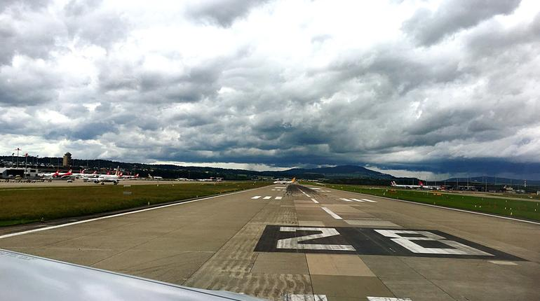 View Of Airport Runway Against Cloudy Sky