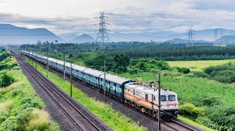 awesome close front engine view of indian railway running on track goes to horizon in green landscape under blue sky with clouds.