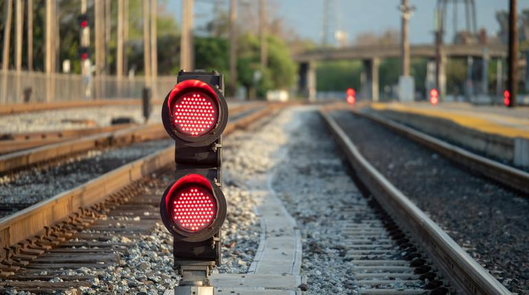 A railroad color position light sits ground level flashing red stop lights with some space to right