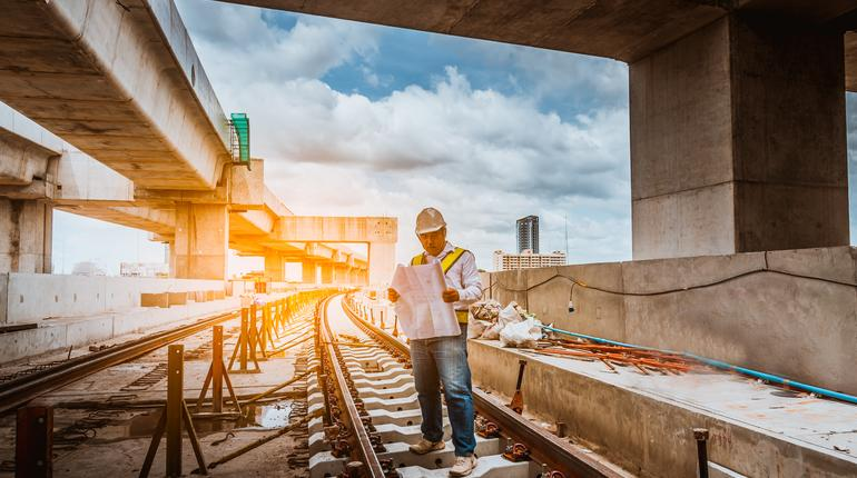 A engineer under inspection and checking construction process railway work on rail train station by Blueprint  on hand . Engineer wearing safety uniform and safety helmet in work.