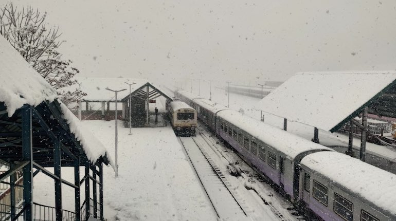 A train rolls into an empty, snow-covered station in Kashmir during the day