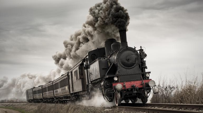 Vintage steam train with ancient locomotive and old carriages runs on the tracks in the countryside